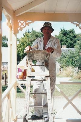 Brian Hieatt painting the verandah of Colonel de Quincey's cottage at Howick Historical Village.; La Roche, Alan; January 2001; P2020.113.02