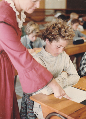 A child and 'teacher' in Pakuranga School in Howick Historical Village during a school visit.; N.Z. Woman's Weekly; 1982; P2021.182.06