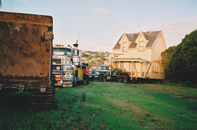 Ace Towing Co. and a Johnson's truck moving away from Puhinui on its new site in the Howick Historical Village. ; Alan La Roche; May 2002; P2020.11.23