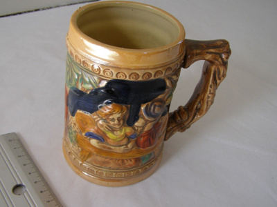 Ceramic mug with relief and painted scenes.