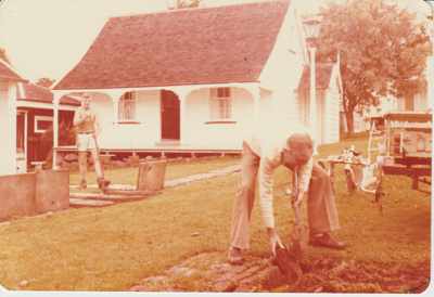 2 men landscaping the area in front of Sergeant Barry's cottage in the Garden of Memories,; La Roche, Alan; c1975; 2019.094.05