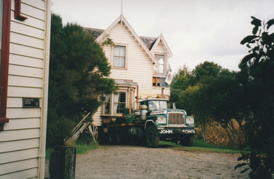A Johnson's Heavy truck and trailer moving Puhinui to its new site in the Howick Historical Village. About to pass Pakuranga School. ; Smith, Malcolm; May 2002; P2020.06.03