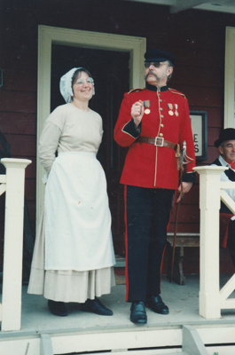 Barbara Doughty in costume and a Fencible soldier in uniform at the opening of the Howick Arms Hotel in Howick Historical Village, during a Winter Festival. ; 28 August 1994; P2021.105.04