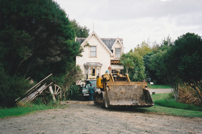 A bulldozer, showing the driver, preparing the way for a Johnson's Heavy truck and trailer to move Puhinui to its new site in the Howick Historical Village.; Alan La Roche; May 2002; P2020.11.32