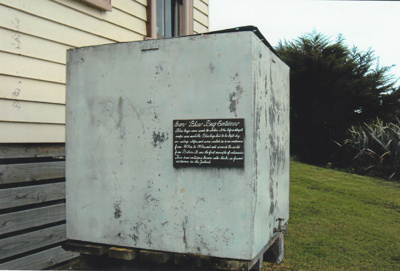 An iron container on display behind Puhinui.; La Roche, Alan; 2010; P2021.103.01