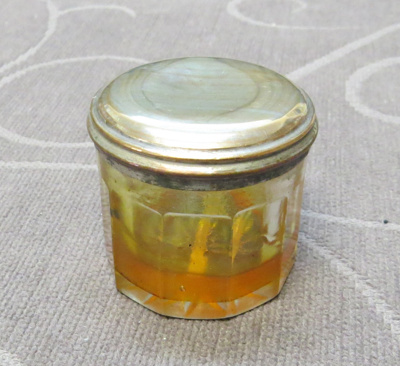 Small round glass pot with silver lid.