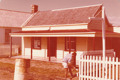 Alan Garvan painting the picket fence outside Brindle Cottage.; February 1980; P2021.26.03