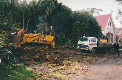 A bulldozer making a road for a House Removals truck truck passing Pakuranga School. A sign for the Forge is on the extreme left foreground.; Smith, Malcolm; May 2002; P2020.16.08