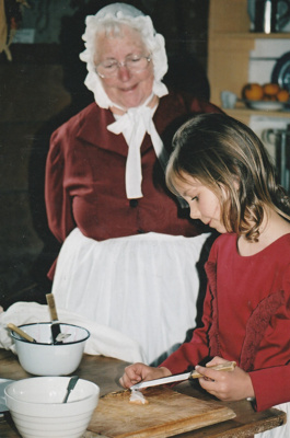 A guide in costume, watching a girl cooking at a table in a cottage on a Live Day in Howick Historical Village. ; La Roche, Alan; P2021.98.11