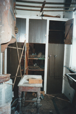 Puhinui laundry area off the  kitchen, before restoration, showing cupboards, exposed pipes, a sink, table, ceiling and walls.; Alan La Roche; May 2002; P2020.11.44
