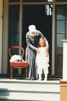Jeanette Claridge dressing Amelie  on the verandah of Puhinui on an HHV Live Day. Marin Burgess is the compere.; Palmer, Ros; October 2003; 2019.198.08