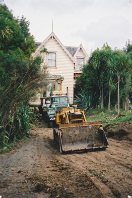 A bulldozer preparing the way for a Johnson's Heavy truck and trailer to move Puhinui to its new site in the Howick Historical Village.; Alan La Roche; May 2002; P2020.11.05