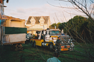 Ace Towing Co. and a Johnson's truck moving Puhinui onto its new site in the Howick Historical Village. ; Alan La Roche; May 2002; P2020.11.14