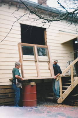 Alan la Roche and David Wardlaw (builder) refitting a window in Puhinui after the move.; Alan La Roche; Sept 2003; P2020.11.18