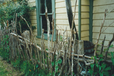 A close-up of Maher-Gallagher Cottage in the Howick Historical Village, showing a ti-tree fence..; La Roche, Alan; 2000; P2020.92.01