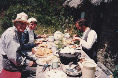 Alan la Roche and two volnteers (in costume) having a meal outside the sod cottage in Howick Historical Village. ; P2021.118.16