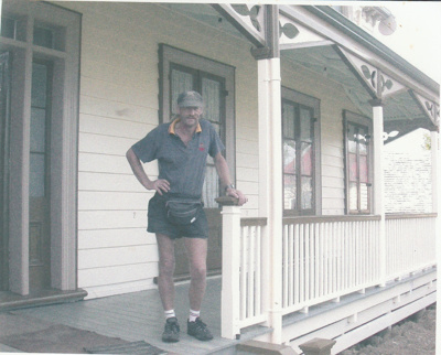John Mustchin, Handyman and builder on the verandah of Puhinui on its new site in the Howick Historical Village.; Alan La Roche; March 2003; P2020.13.01