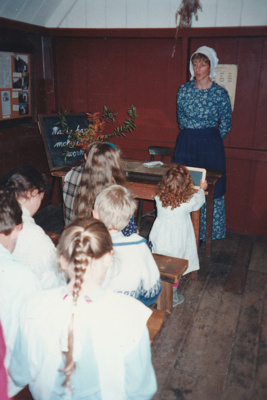 Children and a teacher, in costume, in the Dame School at Howick Historical Village.; 1995; P2021.59.03