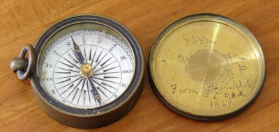 Compass, with a brass lid. It has a brass knob and...