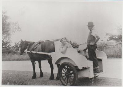 Ken Kelsey driving Ren Wiseman in his milk float.; c1945; 2017.451.37