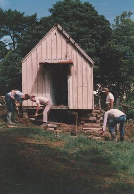 Four men placing the Dame School in position at Howick Historical Village.; La Roche, Alan; June 1990; P2021.61.09
