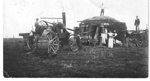 Black and white photographic postcard of traction engine threshing wheat; 1909; 10023