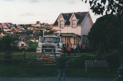 A Mack truck in front of half of Puhinui on its new site in the Howick Historical Village. People are watching. Highland Park housing is behind.; Smith, Malcolm; May 2002; P2020.16.18