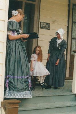 Jeanette Claridge with Amelie  on the verandah of Puhinui on an HHV Live Day. Marin Burgess is the compere.; Palmer, Ros; October 2003; 2019.198.09