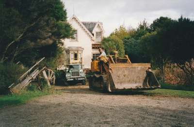 A bulldozer making a road for a  Johnson's Heavy truck and trailer moving Puhinui to its new site in the Howick Historical Village. An old wagon is on the left.; Smith, Malcolm; May 2002; P2020.16.07