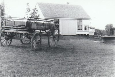 A cart outside Wagstaff's Forge in Howick Historical Village.; La Roche, Alan; 1982; P2020.150.02