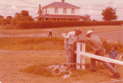 Alan la Roche and Arthur White erecting the flagpole in Howick Historical Village.; c1979; P2021.114.01