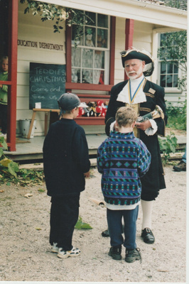 Ron Fryer, as the Town Crier talking with two boys outside Brindle Cottage.; 2019.132.05