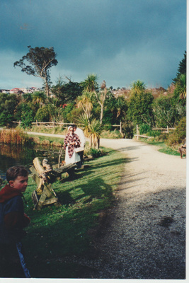 Visitors and a guide in costume on the banks of the pond in the Historic Village; O'Halloran, Esme; 1/08/1995; 2019.128.02