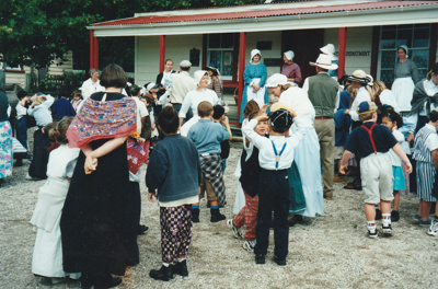 A group of school children and guides, in costume, outside Brindle Cottage in Howick Historical Village.; 1995; P2021.107.19