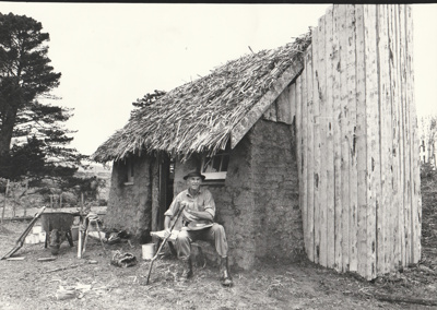 Arthur White in front of the Sod Cottage, Howick Historical Village  ; 6 November 1980; P2020.43.15