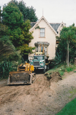 A bulldozer preparing the way for a Johnson's Heavy truck and trailer to move Puhinui to its new site in the Howick Historical Village.; Alan La Roche; May 2002; P2020.11.27