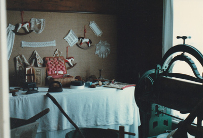A sewing exhibition in the front room of Johnson's cottage in Howick Historical Village.; La Roche, Alan; November 1989; P2020.122.01