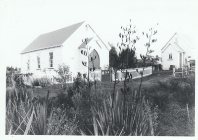 Looking across flax bushes to the Howick Methodist Church and the Ararimu Valley School in the Howick Historical Village.; 1981; P2020.34.07