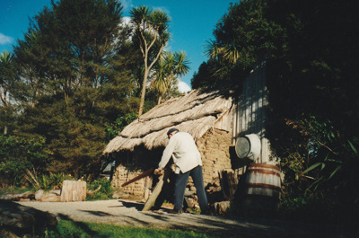 A soldier sawing wood in front of the sod cottage in the Howick Historical Village.; La Roche, Alan; c2000; P2020.50.21