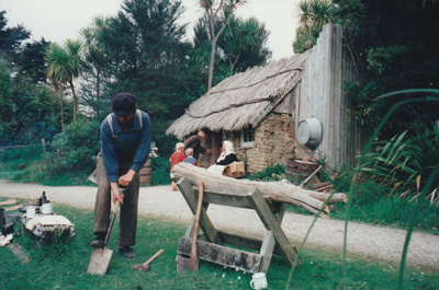 A soldier digging in front of the sod cottage in the Howick Historical Village. Marion Cartwright, in costume, is sitting outside the cottage talking to visitors.; La Roche, Alan; c2000; P2020.50.22