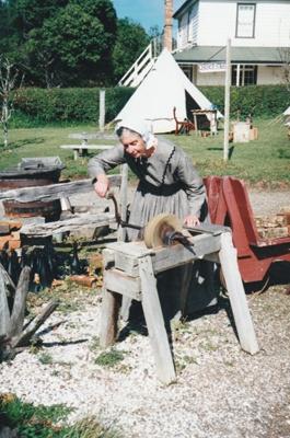 Adrienne Zuppicisch using a grinding stone at Howick Historical Village.; P2021.105.24