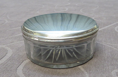 Round glass box with silver lid.
