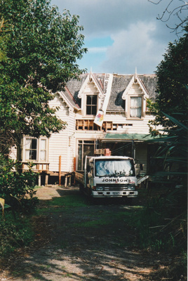 A Johnson's Heavy truck and trailer in front of Puhinui in its new site in the Howick Historical Village. ; Alan La Roche; May 2002; P2020.11.07