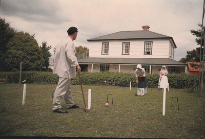 A man and two ladies, all in costume playing croquet on a Live Day  in Howick Historical Village.; Eastern Courier; P2021.121.06