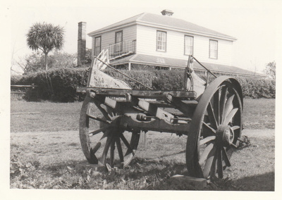 A wagon in state of disrepair at the Howick Historical Village. Bell House is in the background.; September 1980; P2020.18.13
