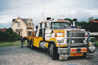 A Truck Towing  and a Johnson's truck moving away after delivering half of Puhinui onto its new site in the Howick Historical Village.; Alan La Roche; May 2002; P2020.11.22