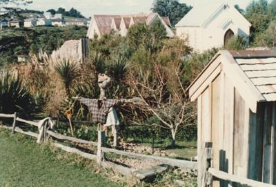 A scarecrow in the garden behind White's Store. ; Harris, Josie; P2020.87.01