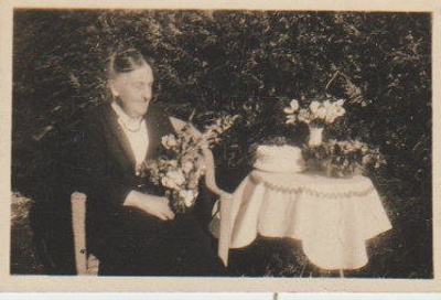 An elderly lady with flowers and a birthday cake; c1910; 2018.336.16