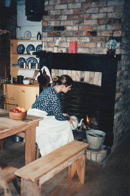 A guide in costume boiling water over the fire in Michael Ford's cottage, in the Howick Historical Village. ; La Roche, Alan; 2004; P2021.049.9