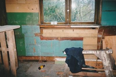 Puhinui kitchen before restoration, showing bare walls, a window, sawhorse and debris.; Alan La Roche; May 2002; P2020.14.07